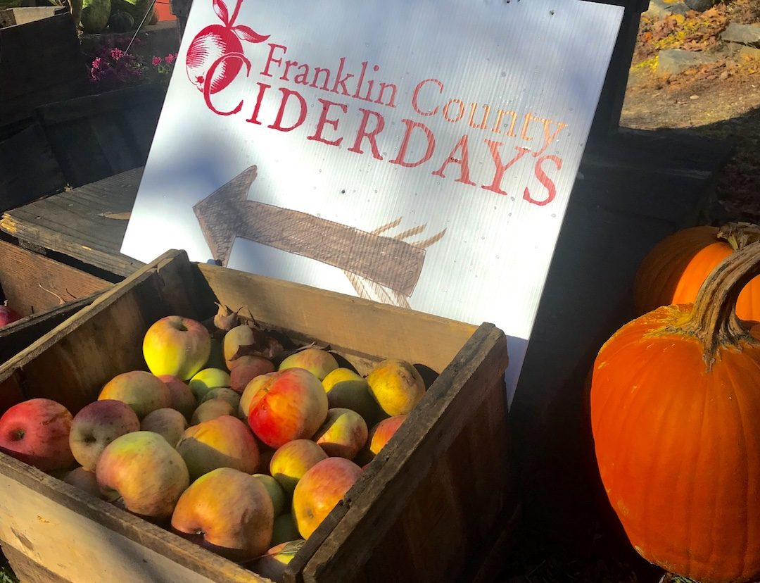 Franklin County Cider Days Sign with a basket of apples and pumpkins nearby