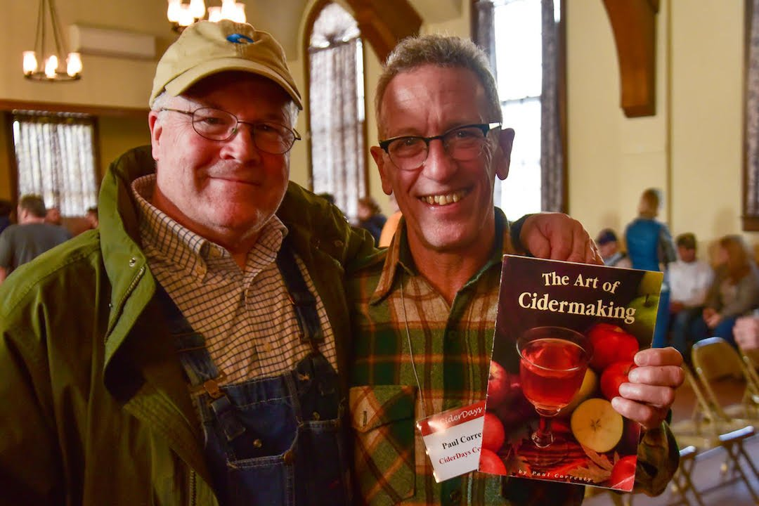 Two Cider Days Attendees holding a cider making book with big smiles