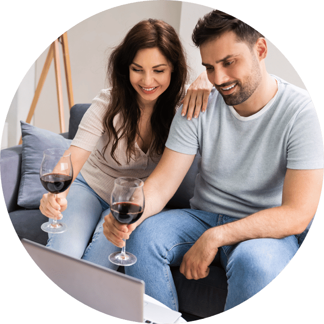 Couple holding wine glass up to computer during virtual event
