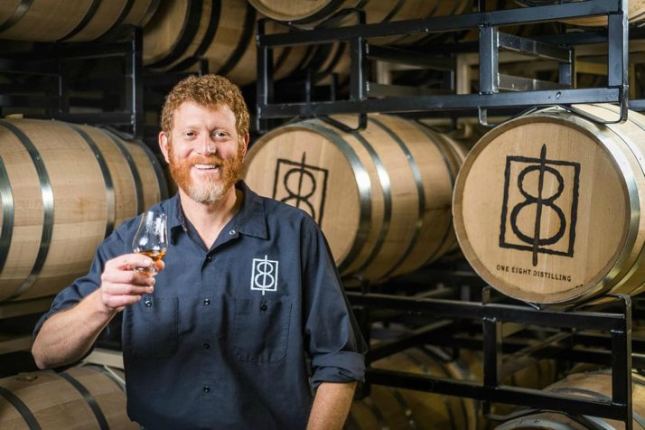 Portrait of One Eight Distillery owner holding glass of whiskey