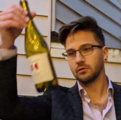 Portrait of Stefan holding wine bottle