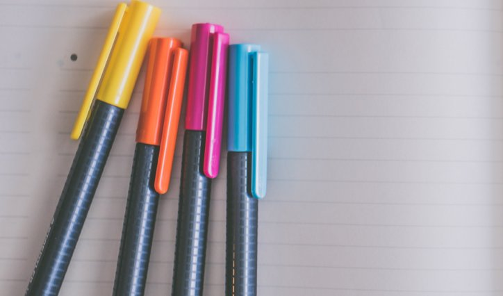 Colorful pens on notebook